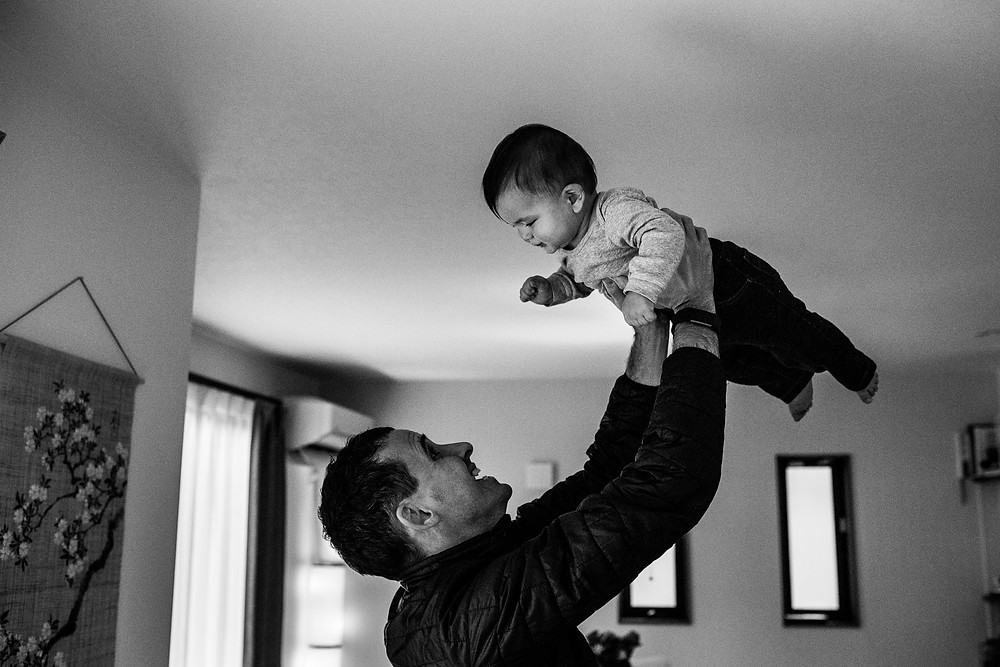 Jesse holds his little boy up high in the air