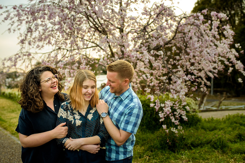 parents and daughter in front of a weeping sakura