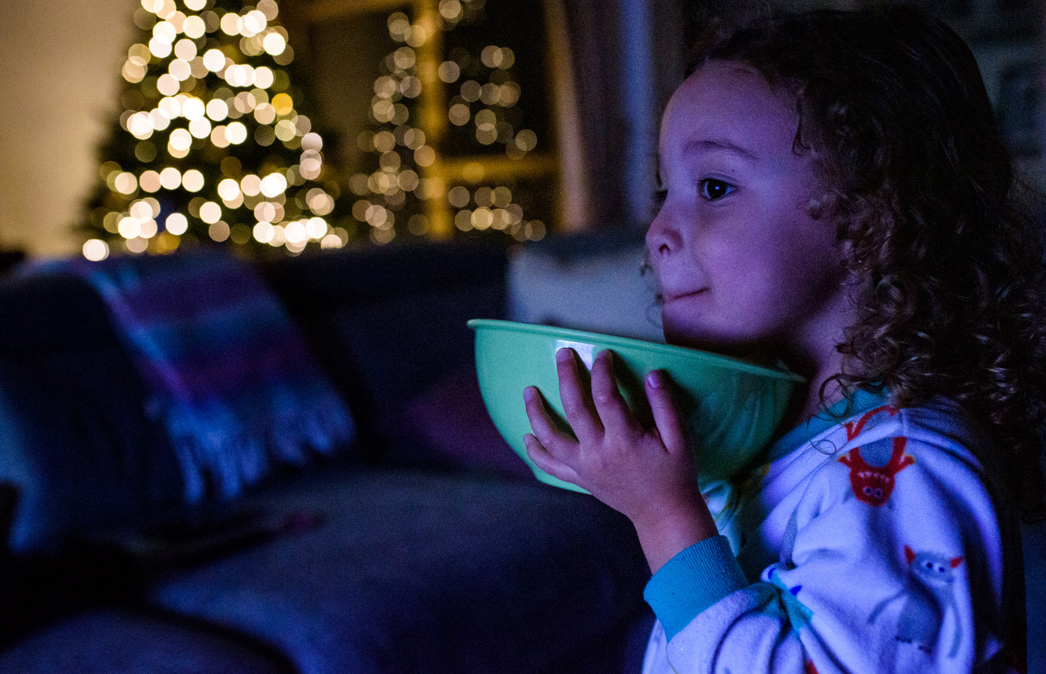 girl eats popcorn in front of the Christmas tree