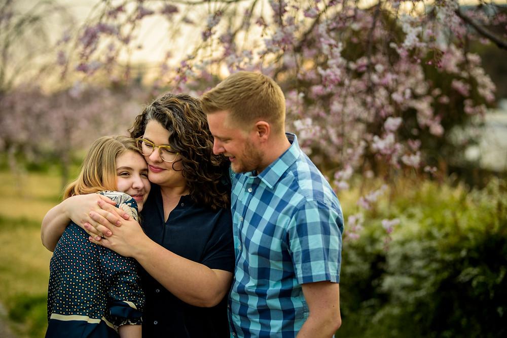 mom hugs daughter in front of the sakura