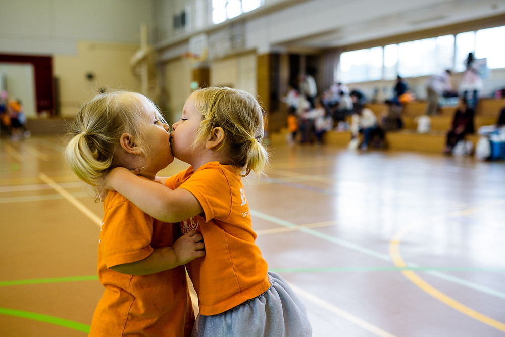 Skye and Clara kiss at the end of sports day in their matching pigtails and orange shirts