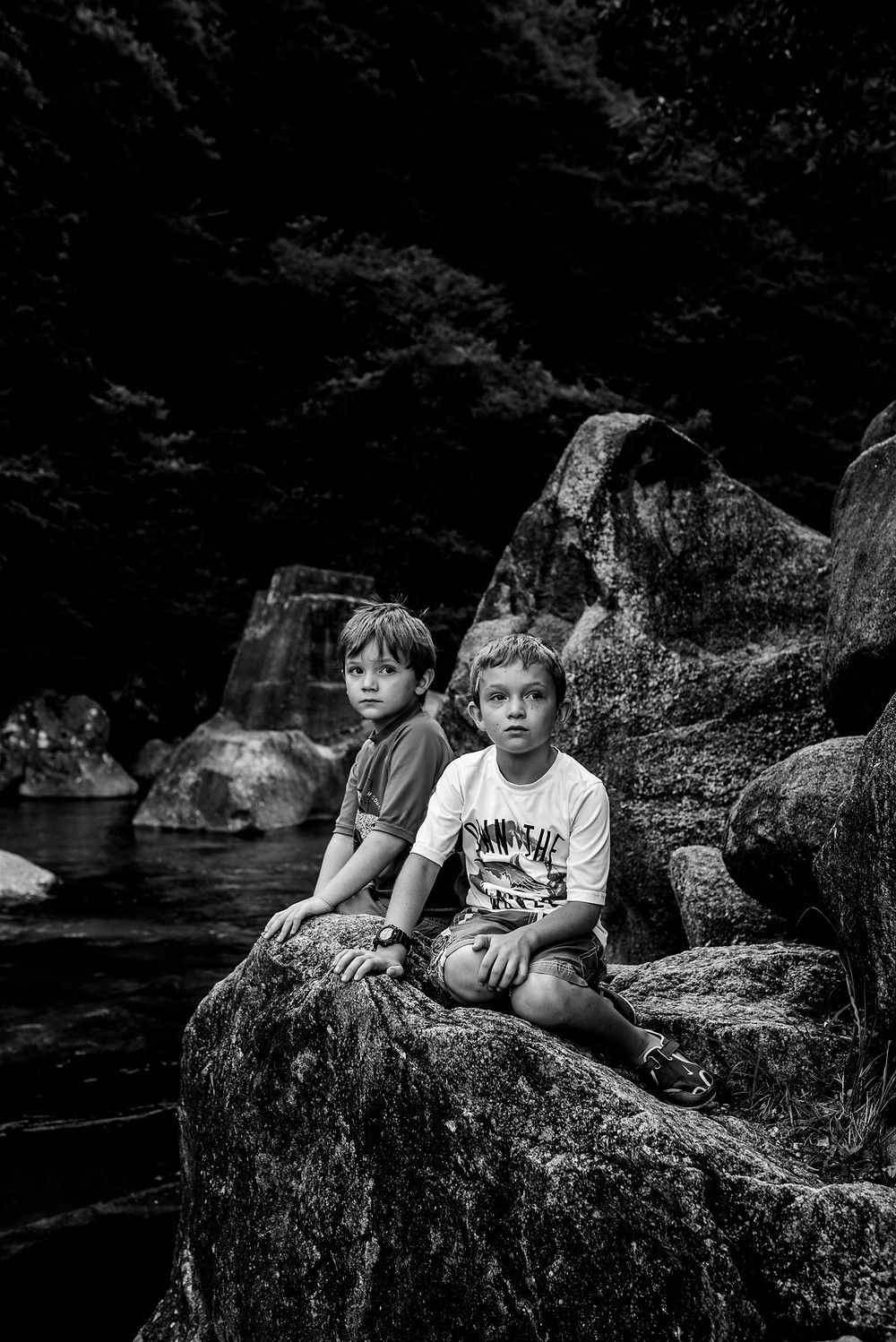 The boys sit on the big rocks by the river
