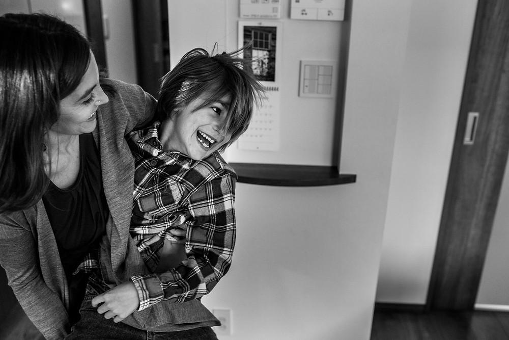 Nicole carries Ezra across the room, both laughing