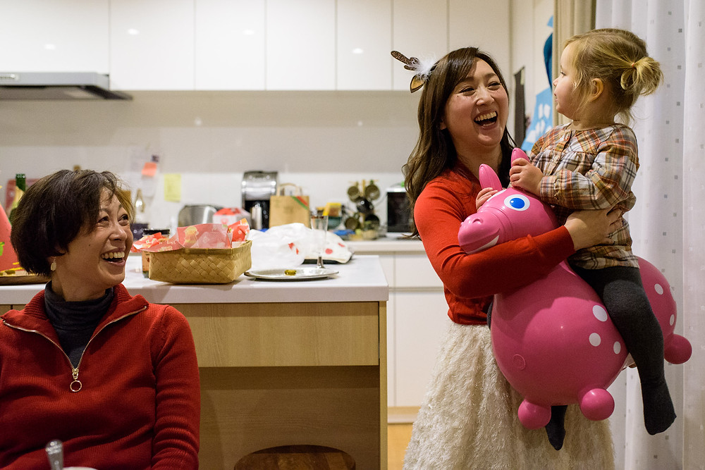 Futaba laughs as her sister Mayu carries Clara around on the bouncy toy