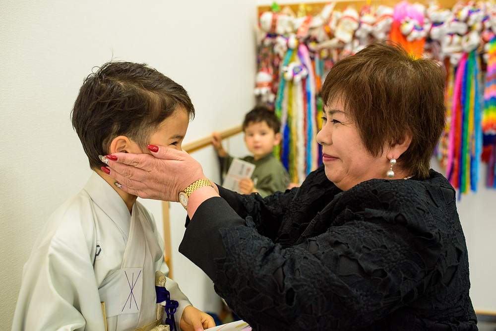 Grandma dresses her grandson in a kimono and grabs his face lovingly