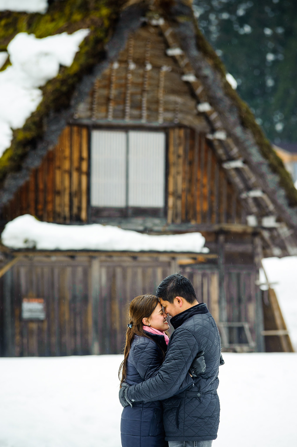 Vertical shot of CJ and Khristel embracing in front of a grass roof home