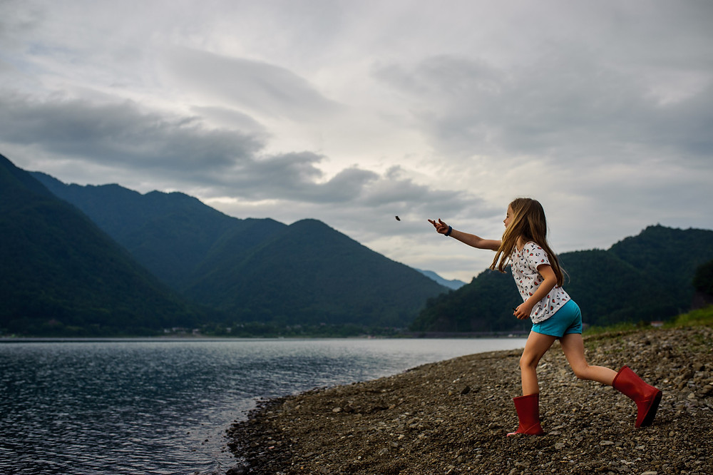 Amelia throwing rocks in the water at Lake Saiko
