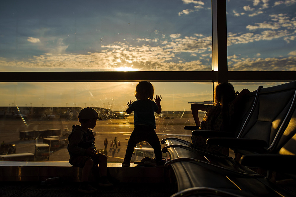 All 3 kiddos watching the  planes go by in the sunset light in the Detroit airport