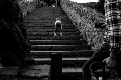 girl crawls up a big set of stone stairs