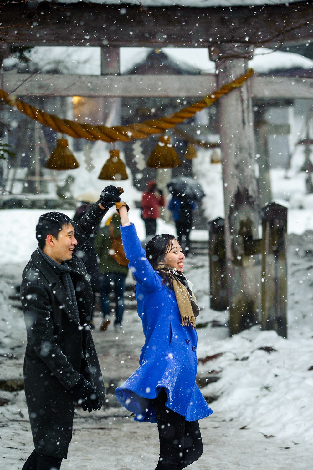 The snow falls around the couple as they dance in front of the torii gate
