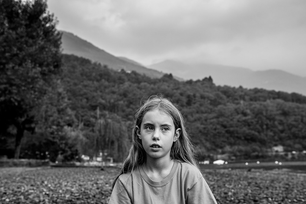 girl thinks while sitting in front of the mountains