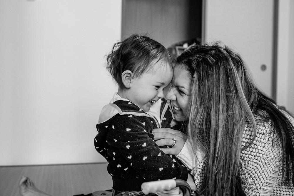 Mom tickles her little girl
