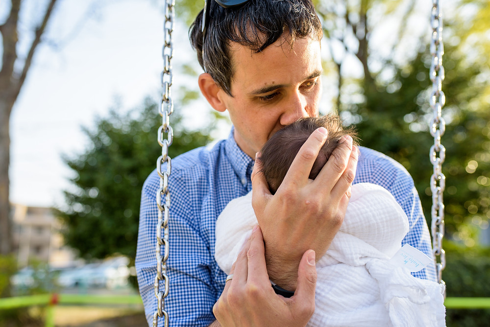Jesse kisses his baby in the swing