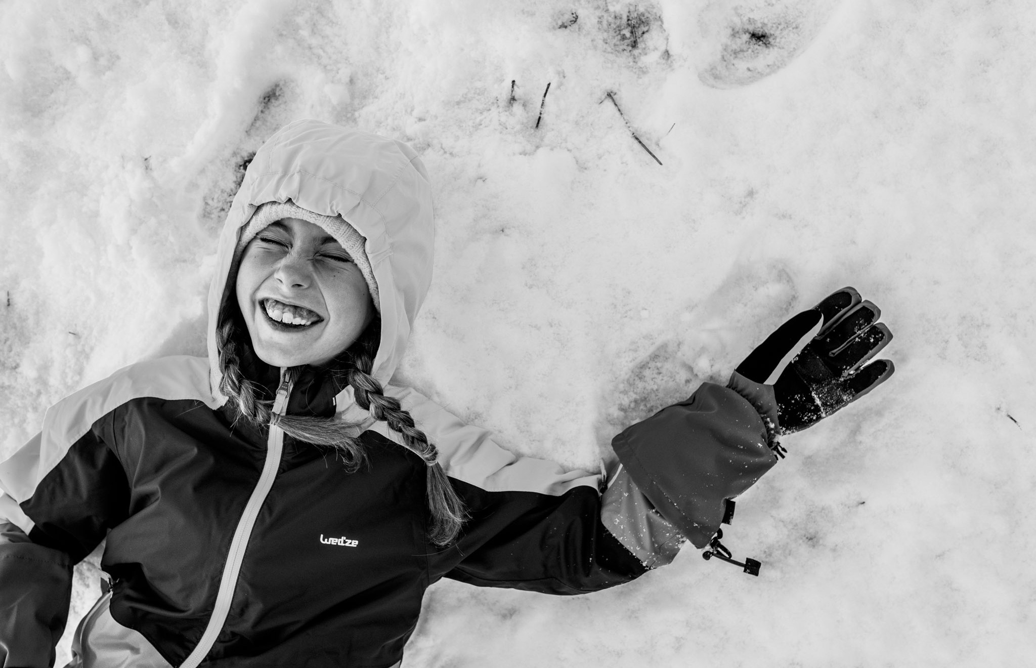 girl smiles happily in the snow after sledding