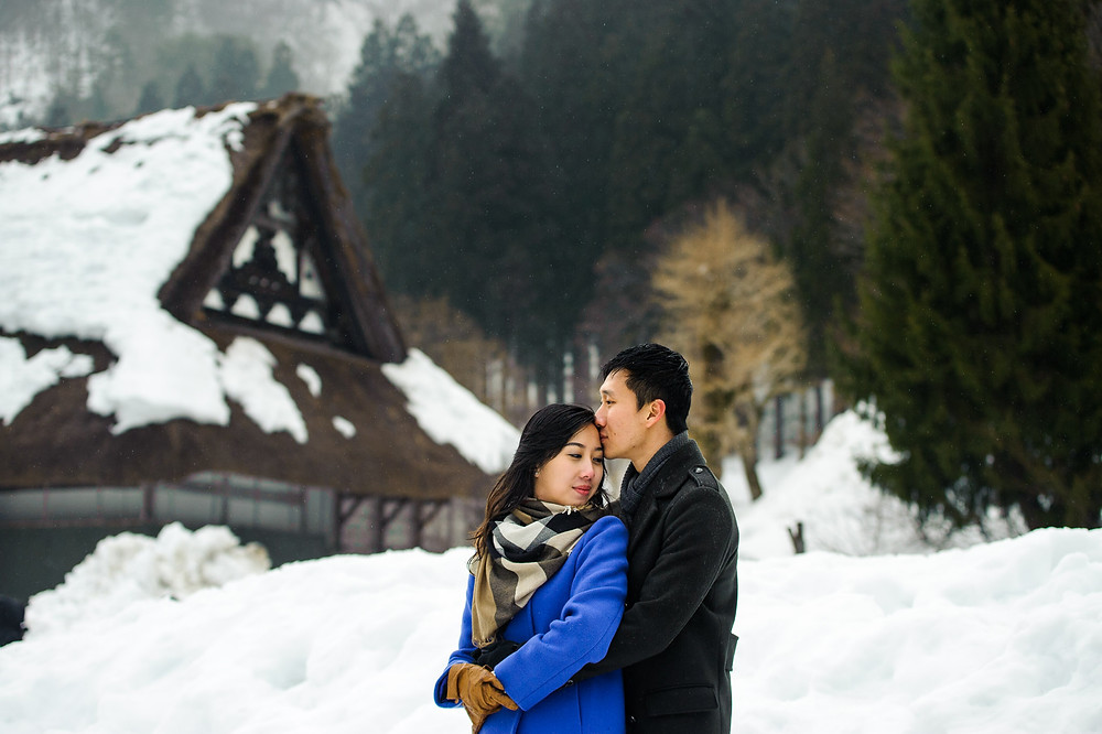 Sin kisses Mira on the forehead in the snow in Shirakawago