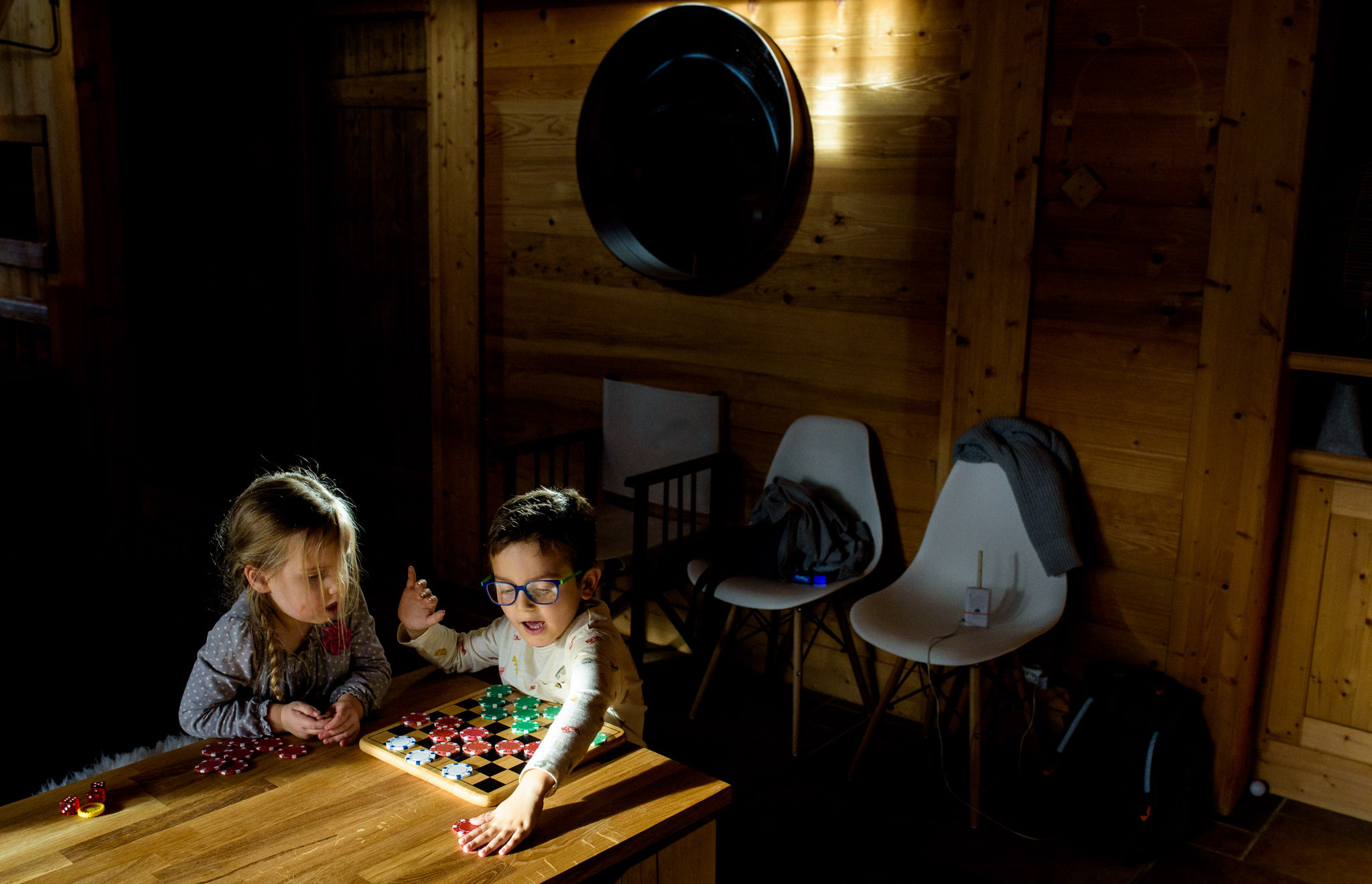 little kids play checkers with poker chips