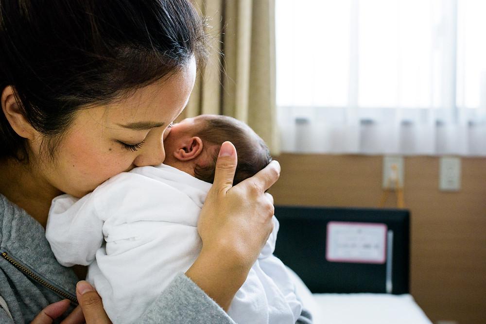 Fukumi snuggles her baby