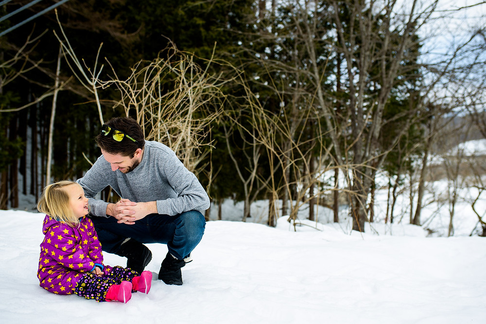 Skye sits in the snow in her purple snowsuit and smiles at her dad