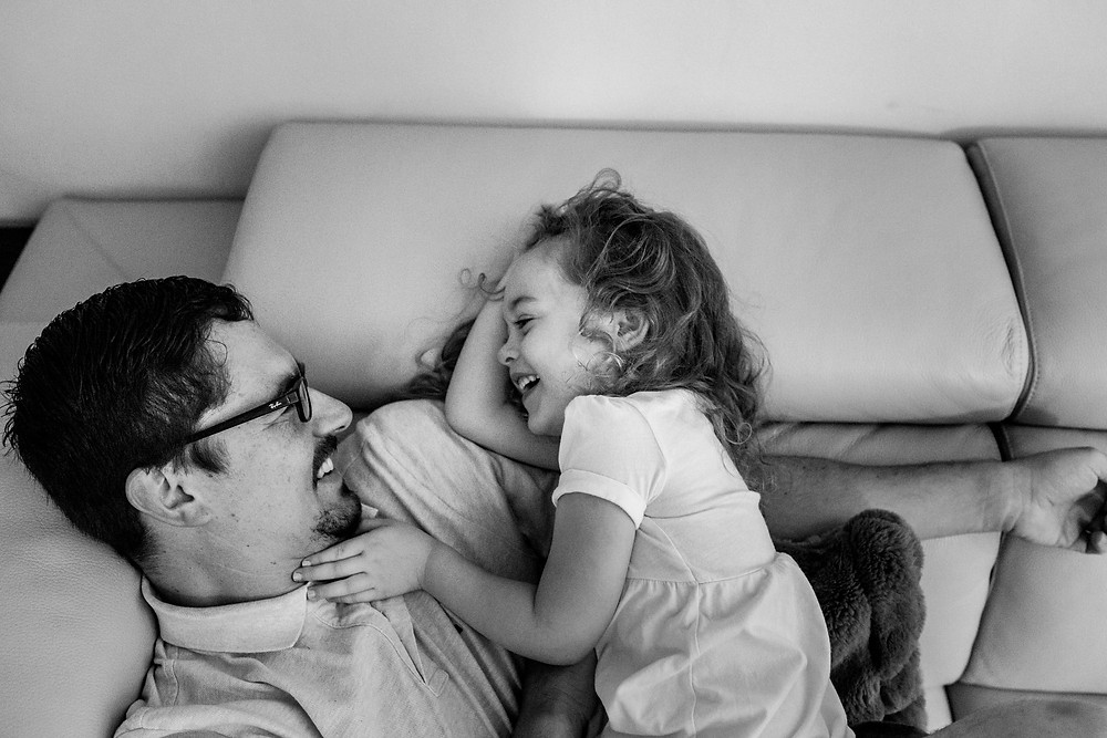 dad and his little girl laughing on the couch