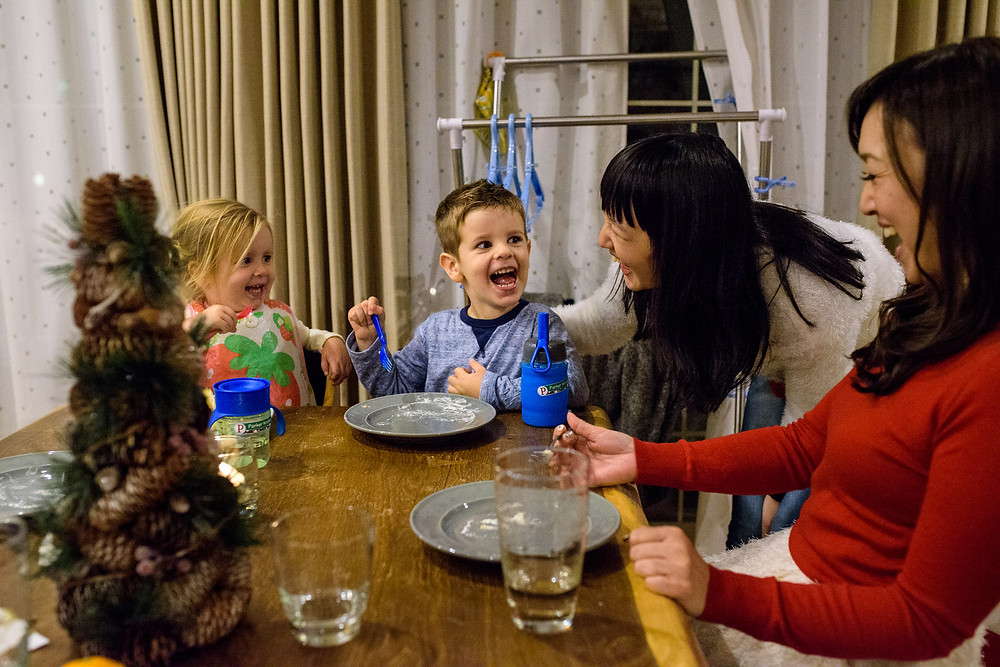 Parker laughs with his sister and neighbors as he finishes his Christmas cake