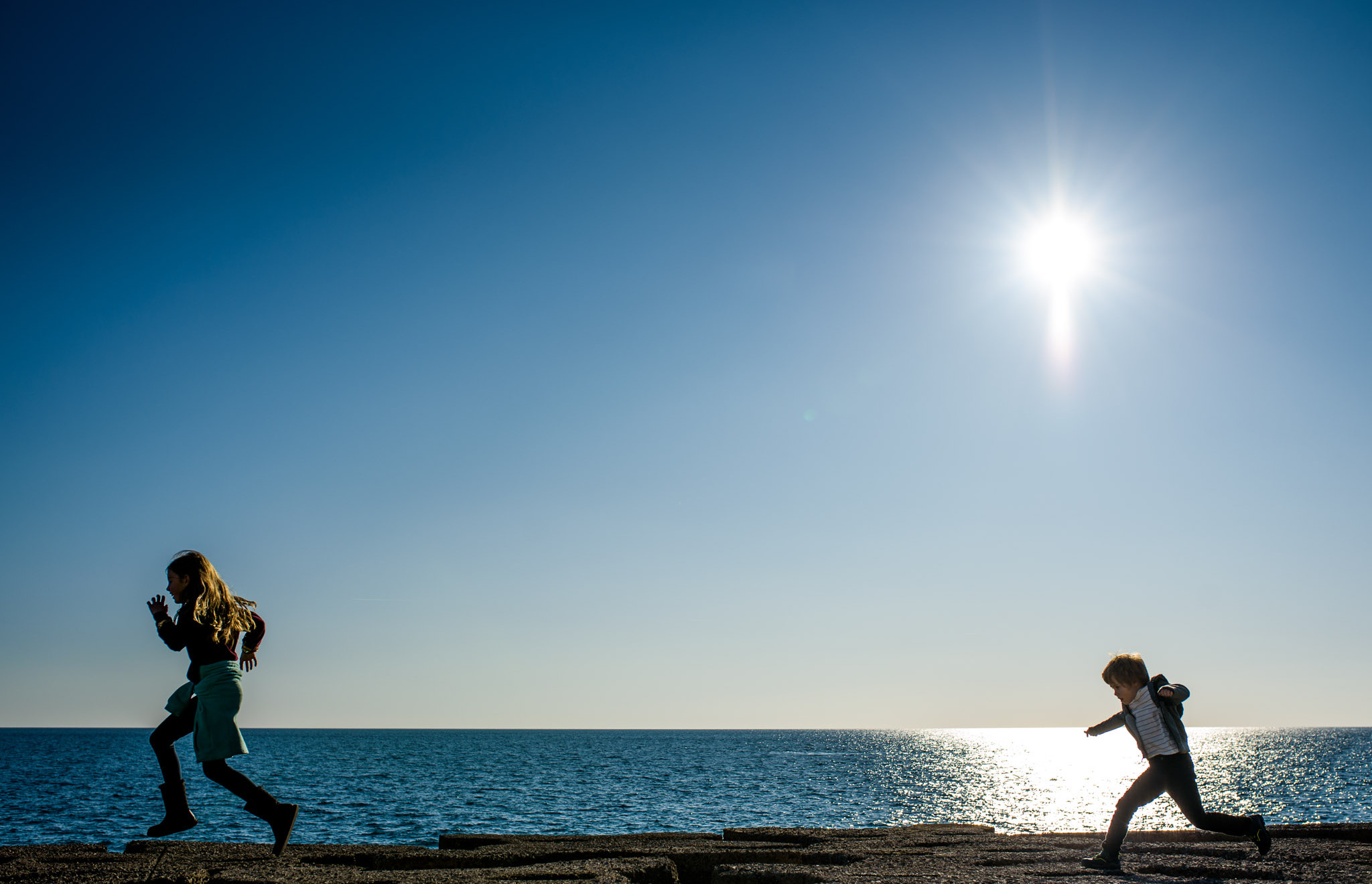 two kids running in the sunlight at the ocean
