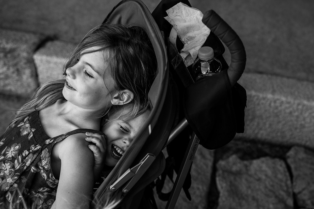 Amelia sits on Dean in the stroller