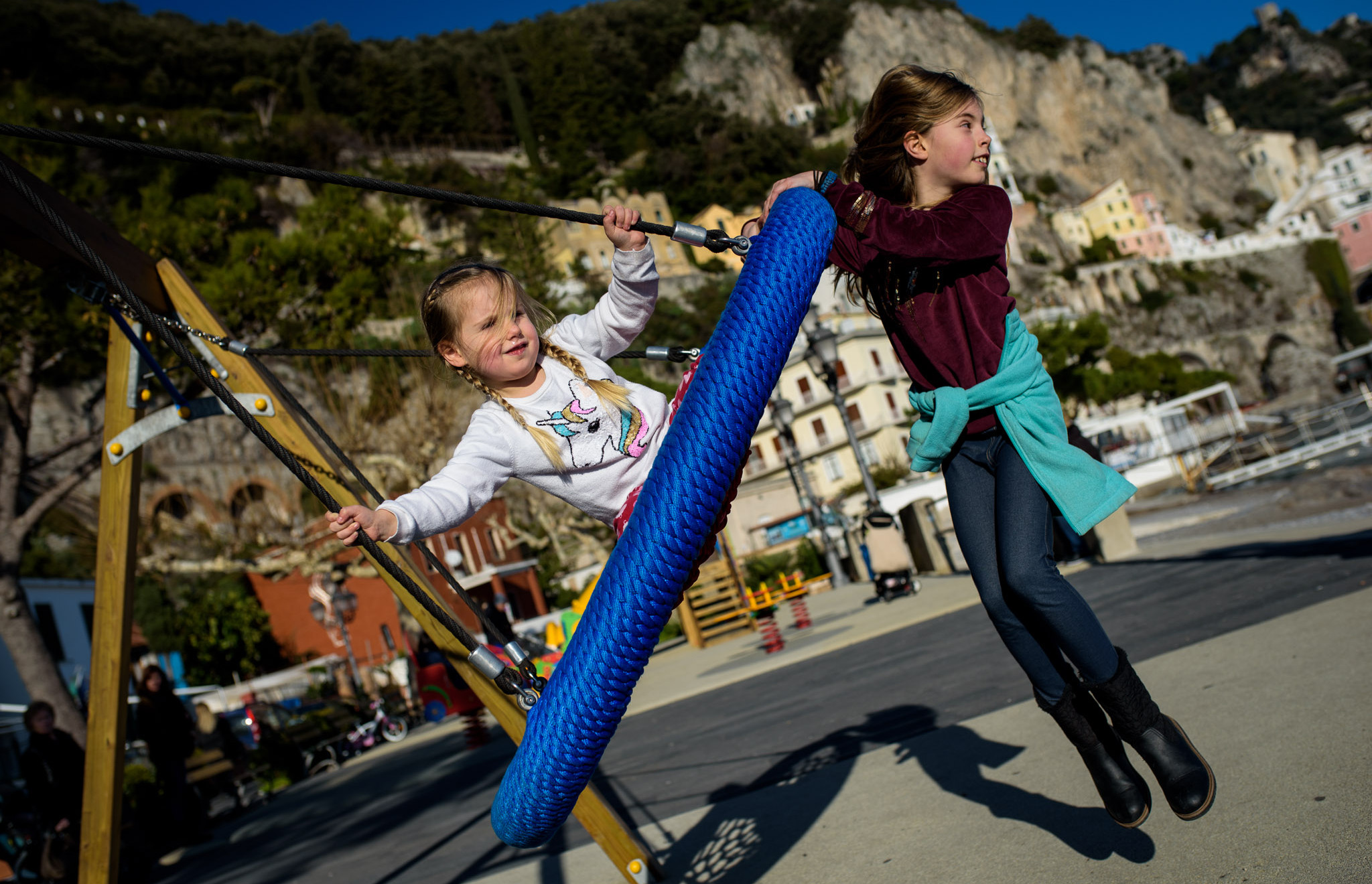 girl swings and big sister pushes