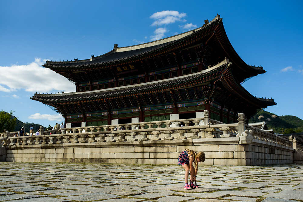 Amelia pulls at the iron circle in the ground in front of the Gyeongbokgung Palace in Seoul