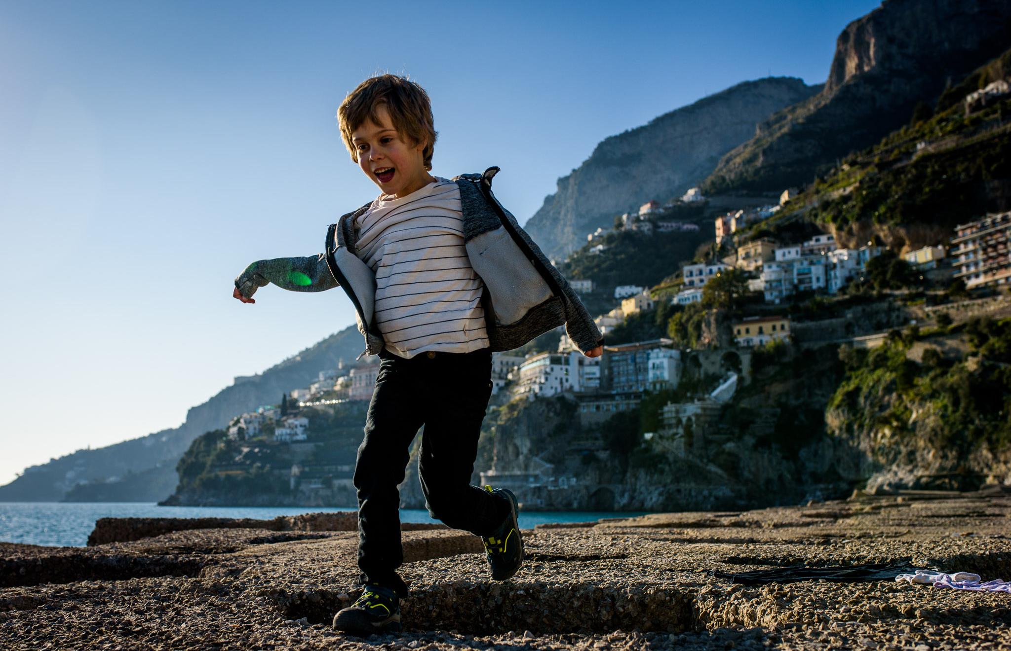 boy runs on the rocks along the coast
