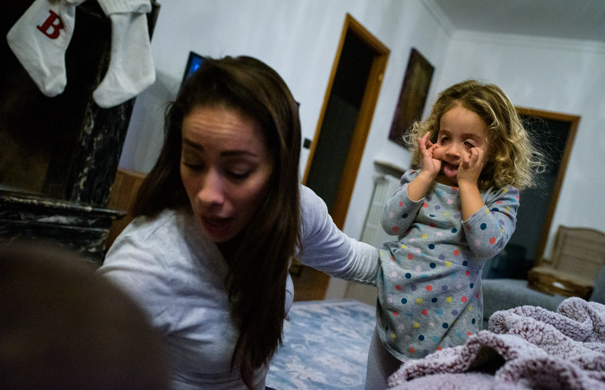 girl makes silly face at mom who's distracted with son