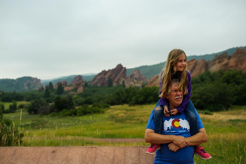 Amelia riding on grandpa's shoulders