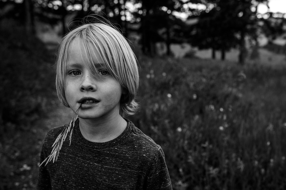 little boy with grass in his teeth