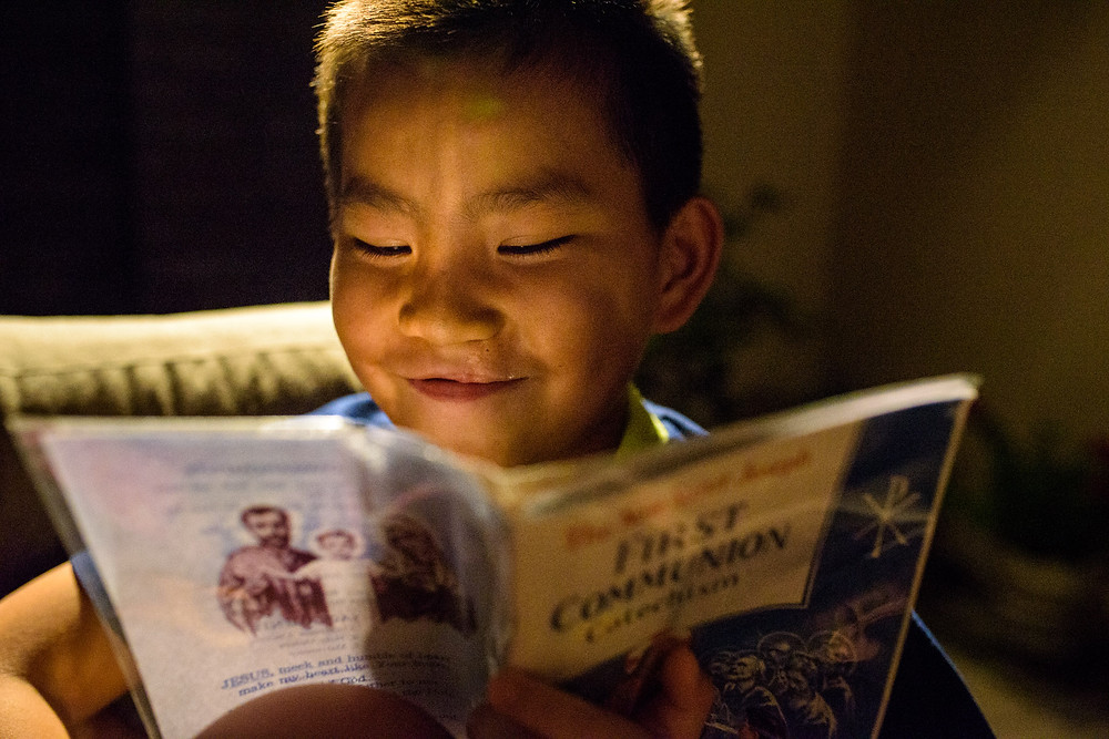 Sen Lin smiles while reading his first communion book