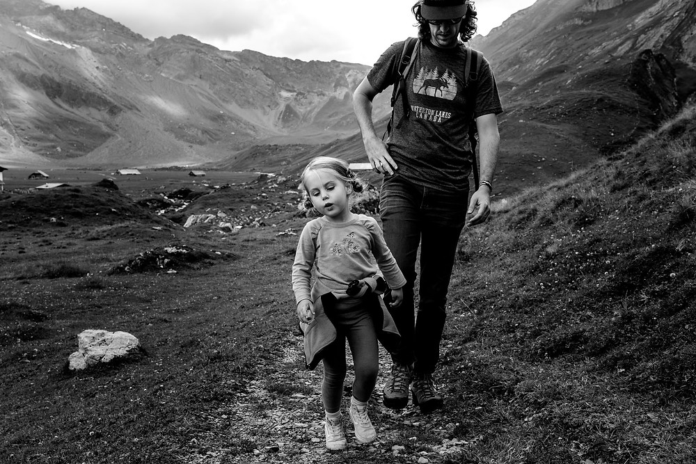 girl and her dad walk in the mountains