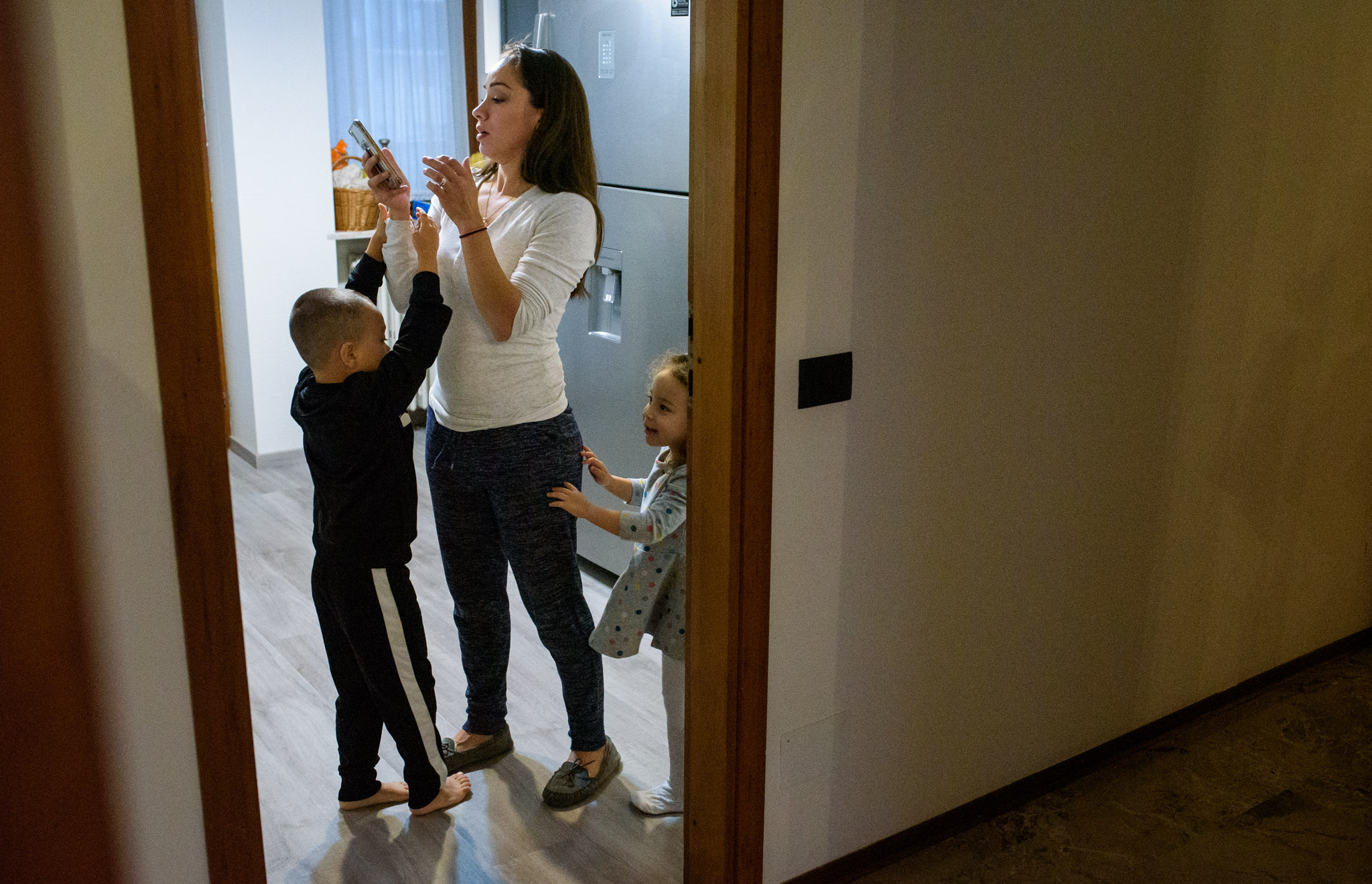 mom tries to focus on her phone while kids hang on her