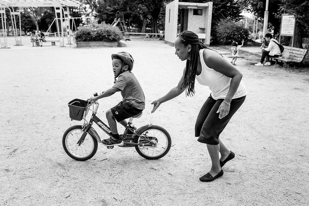Andrea helps Jackson start on the bike