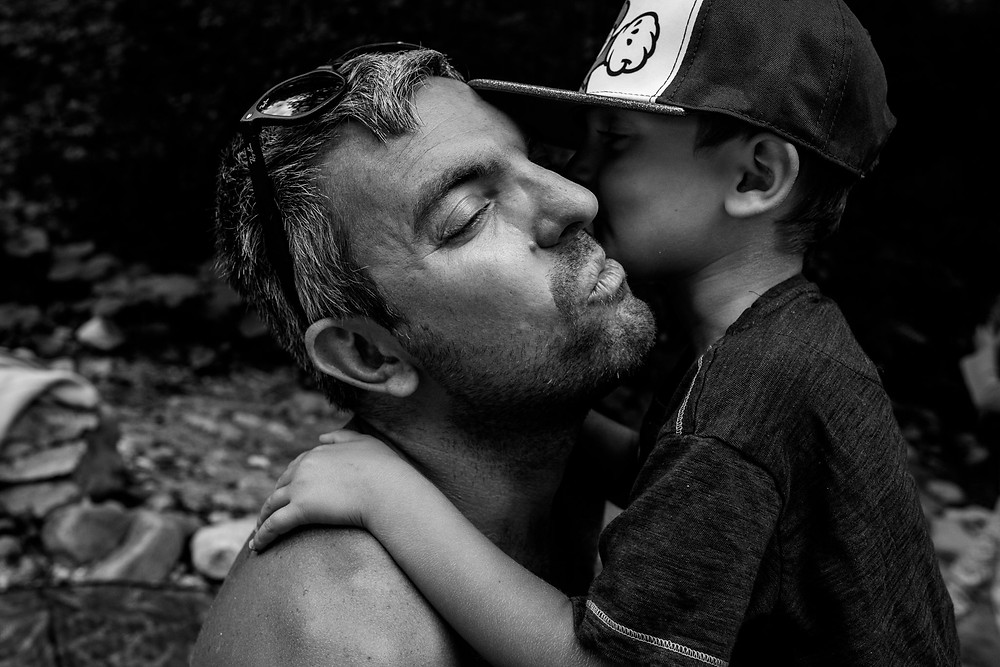 dad getting a kiss from his son at the river