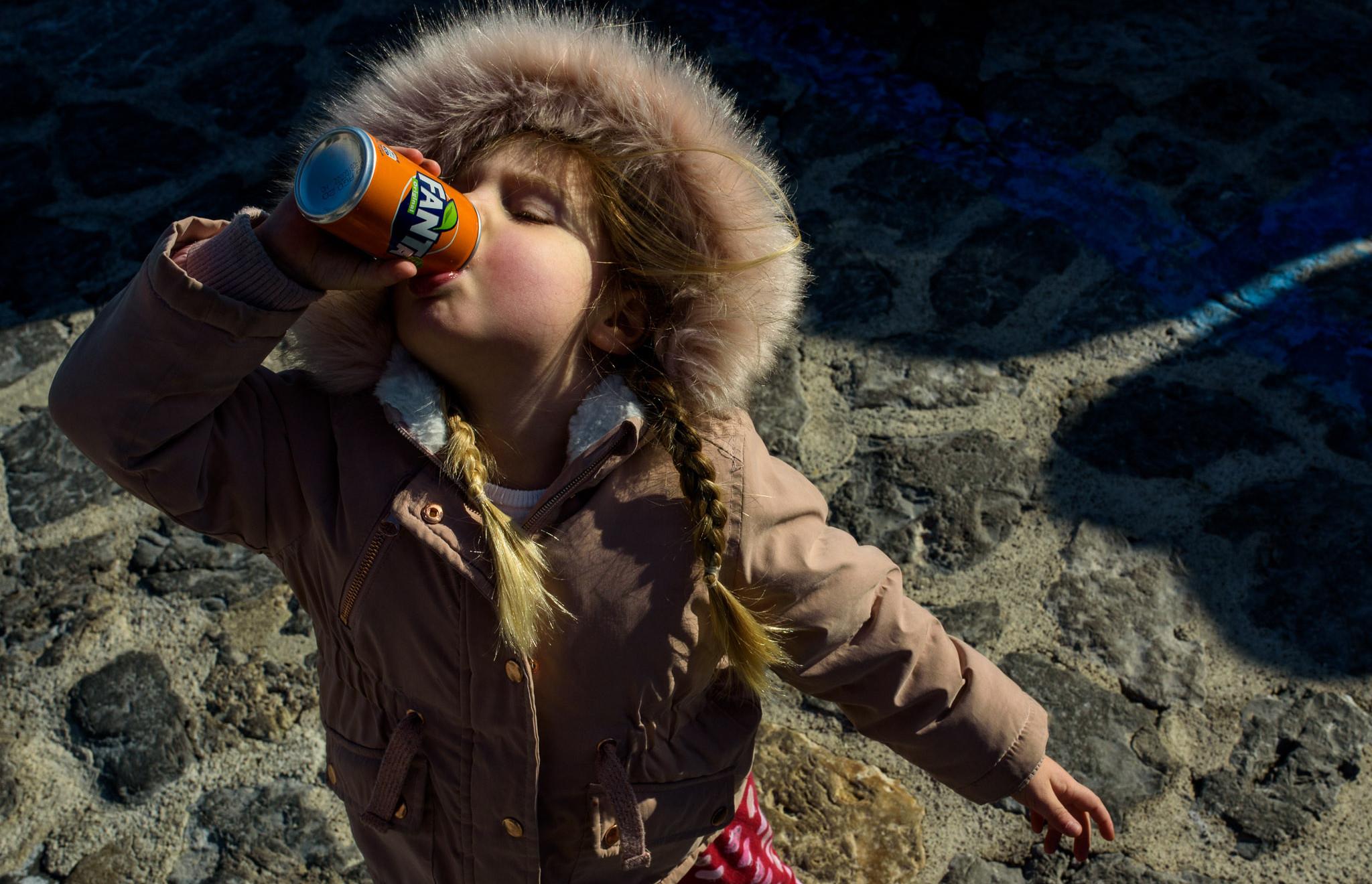 girl drinks Fanta in the sun