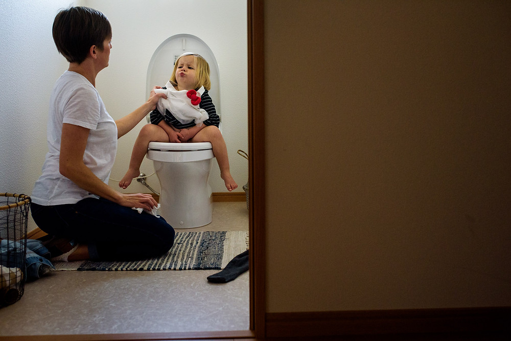 Clara sits on the potty and makes a face