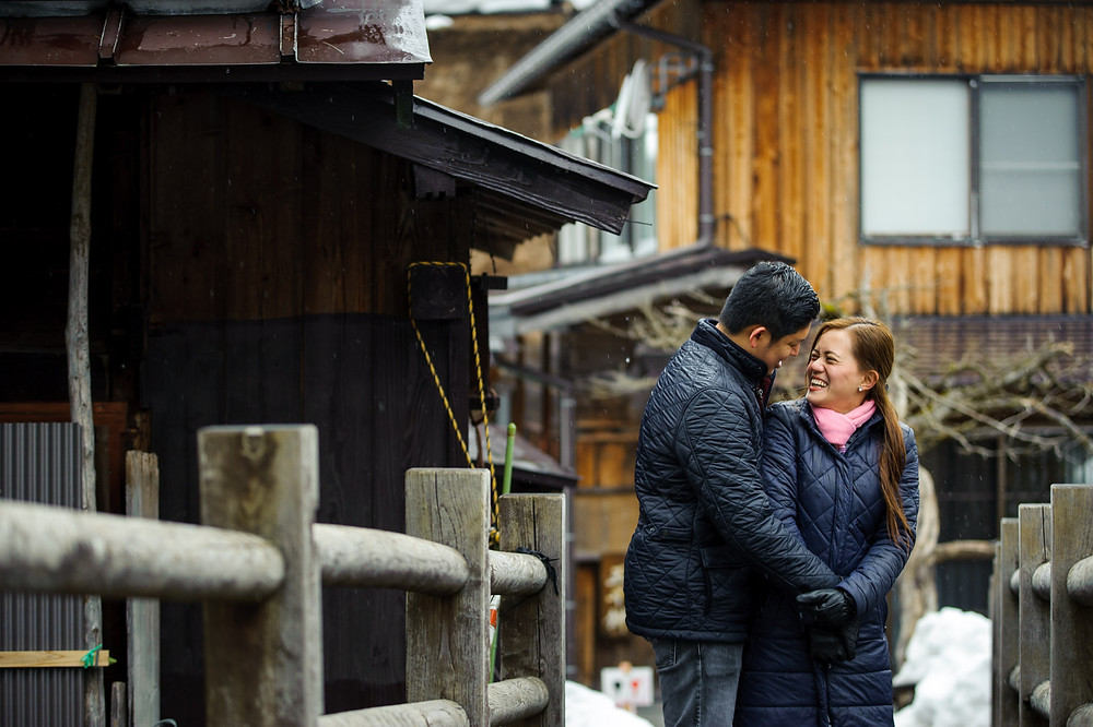Khristel and CJ laugh together on a little bridge in Shirakawago