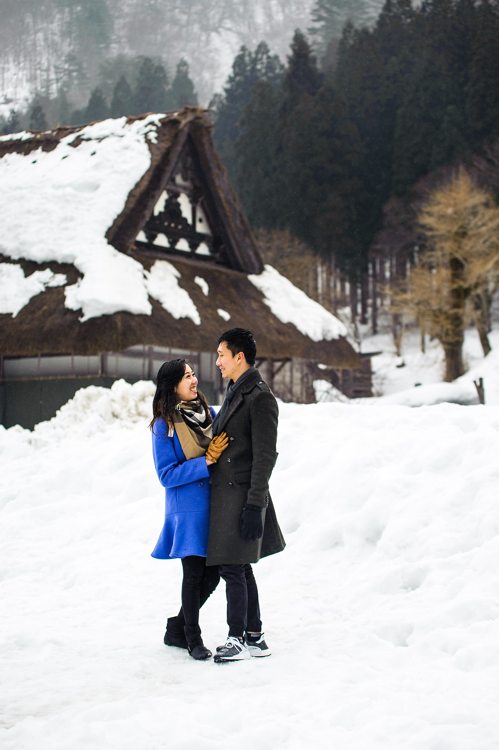 Mira and Sin in front of a snow covered house in Shirakawago