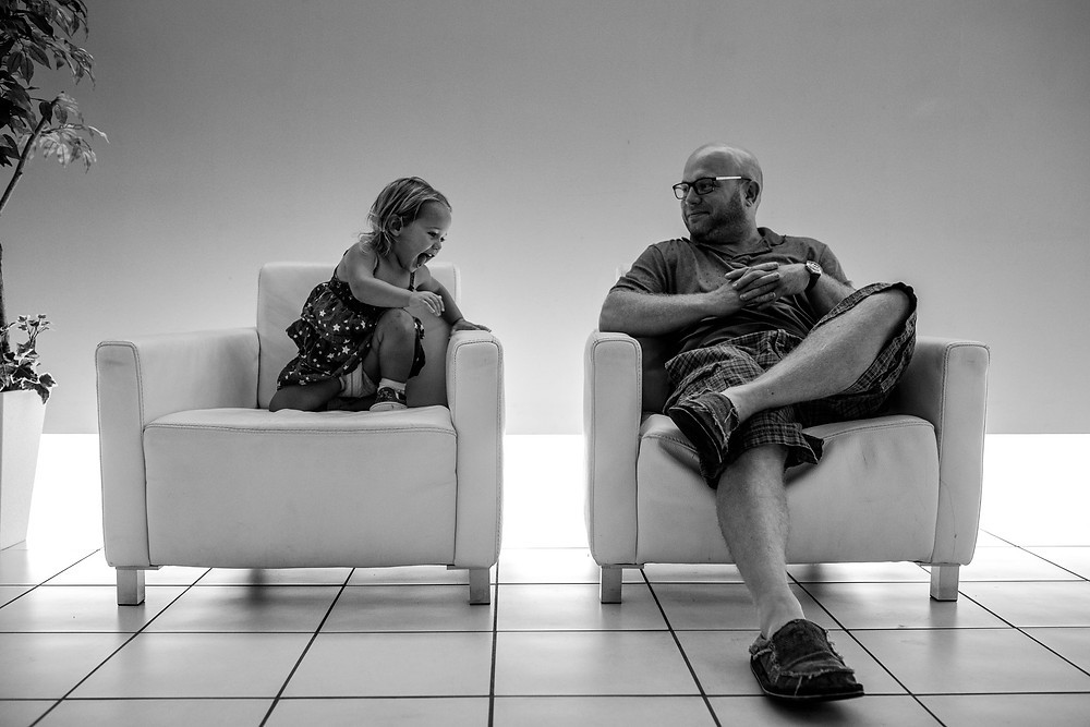 Anna Bella and her dad sit in the lobby chairs