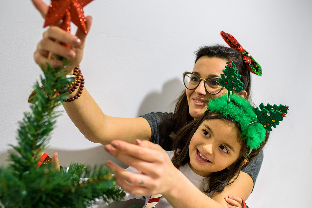 mom and daughter adjust the star on the tree