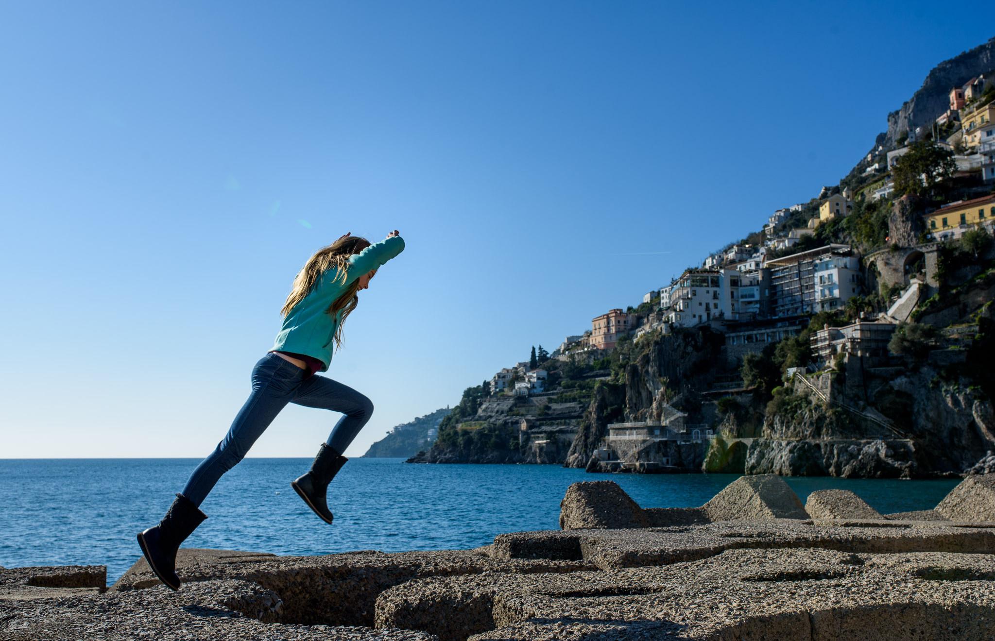 girl jumps on the rocks at Amalfi