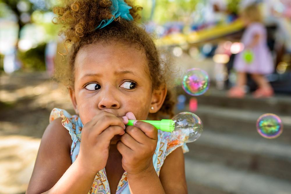 Addison blows sideways bubbles at the park