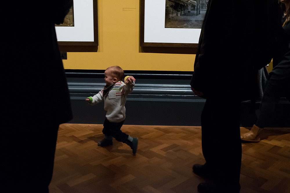 boy running from his parents in a museum
