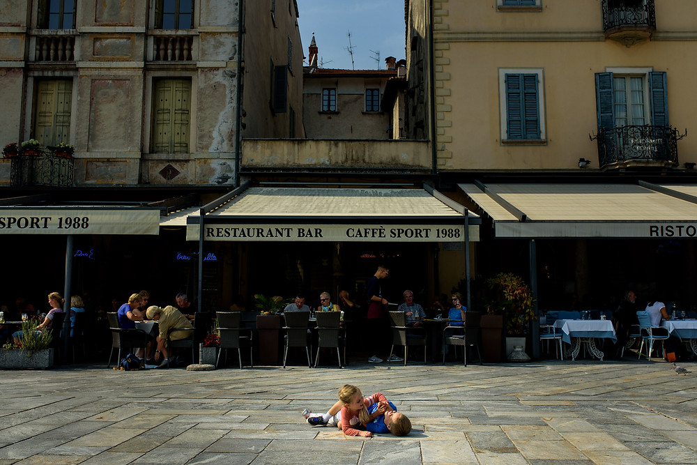 kids wrestling on the ground in front of a restaurant in italy