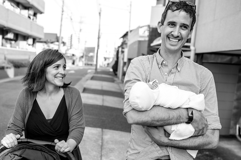 Jesse and Nicole walking down their street with baby in arms