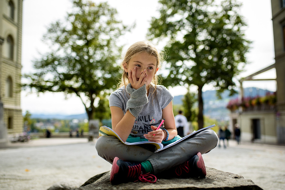 girl sketches on a rock in Bern