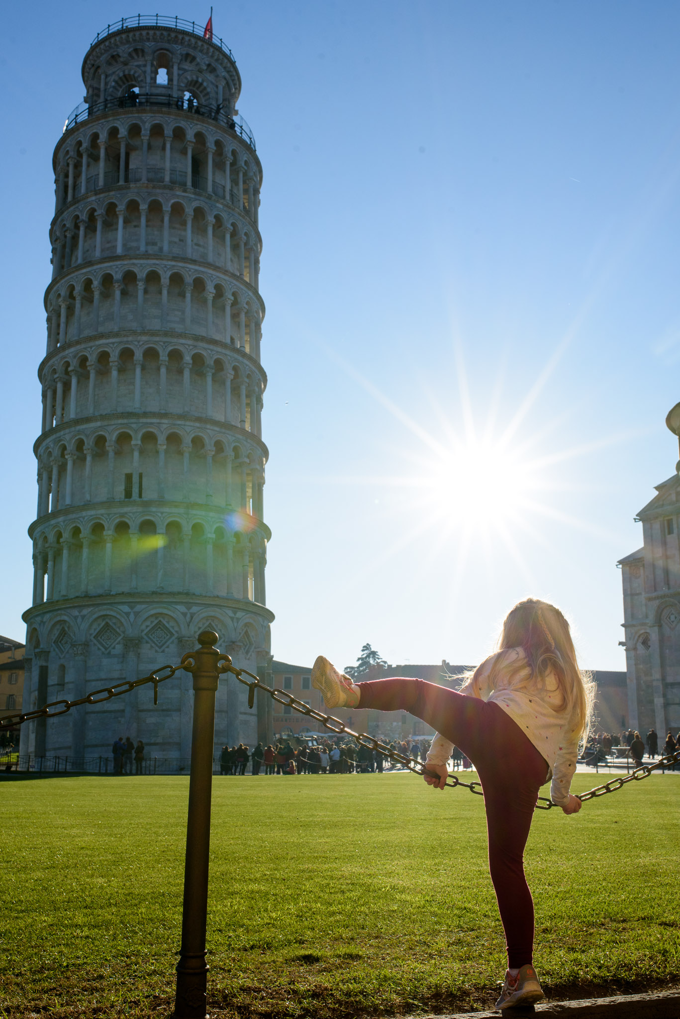 girl tries to climb over fence at Pisa